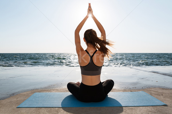 Back view of young attractive girl practicing yoga sitting in pa Stock photo © deandrobot