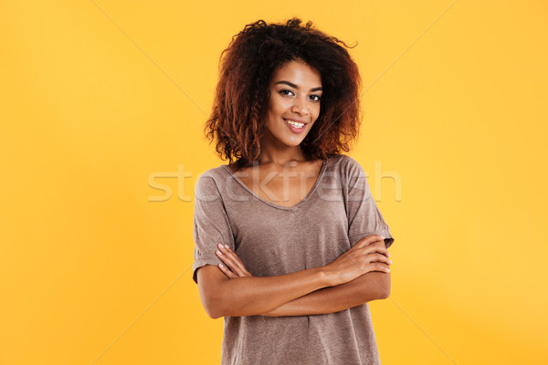 Smiling african woman posing with crossed arms looking at camera Stock photo © deandrobot