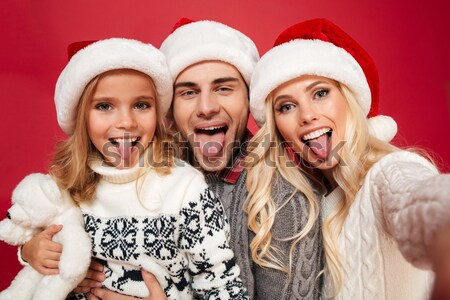 Happy young family in Santa's hat showing peace gesture while ta Stock photo © deandrobot