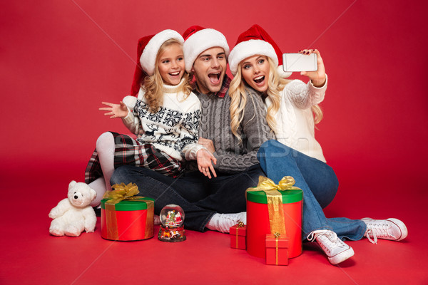 Cute happy young family wearing christmas hats make selfie Stock photo © deandrobot
