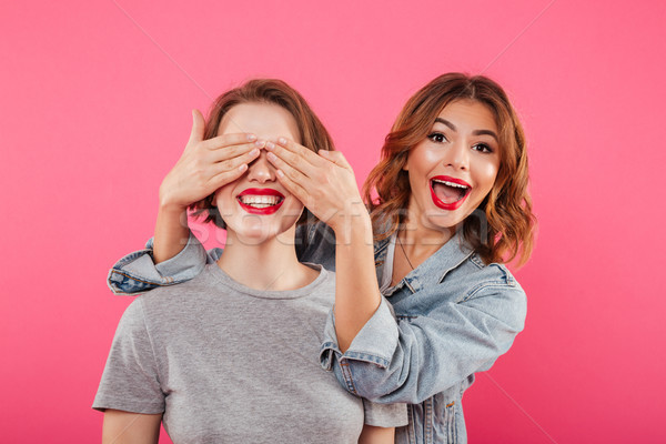 Two ladies friends covering eyes with hands. Stock photo © deandrobot