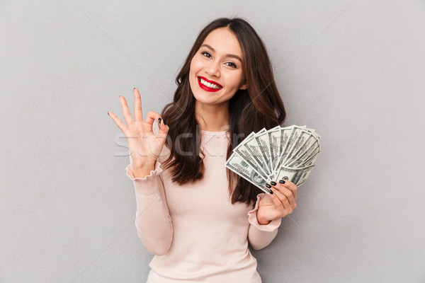 Image of lucky brunette female holding fan of 100 dollar bills b Stock photo © deandrobot