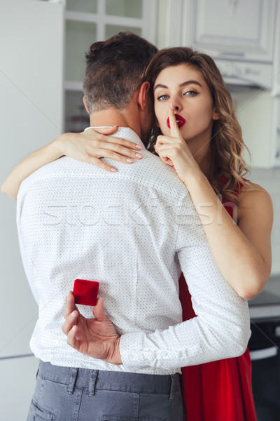 Young man holding box with engagement ring and his woman making silence gesture Stock photo © deandrobot