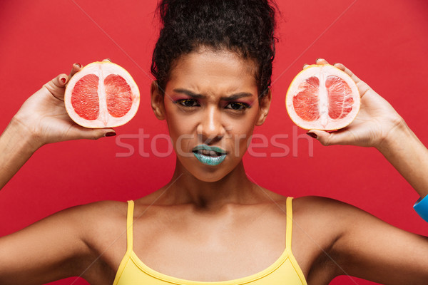 Food image of frowning afro american woman with trendy makeup ho Stock photo © deandrobot