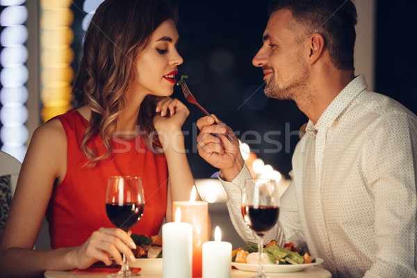 Smiling careful man feed his pretty girlfriend while have romantic dinner at home Stock photo © deandrobot