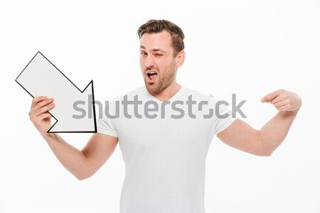 Young man pointing to copyspace. Looking aside. Stock photo © deandrobot
