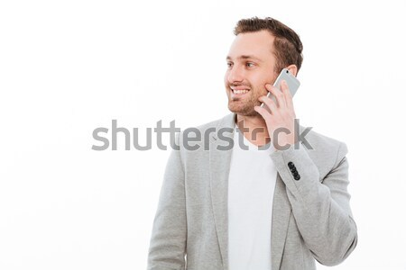 Portrait of businesslike guy in jacket having pleasant mobile co Stock photo © deandrobot