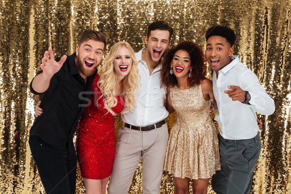 Group of cheerful well dressed people celebrating new year toget Stock photo © deandrobot
