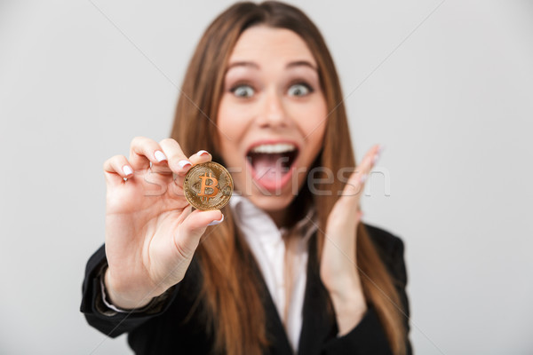 Happy lady with opened mouth looking camera and holding golden bitcoin isolated Stock photo © deandrobot
