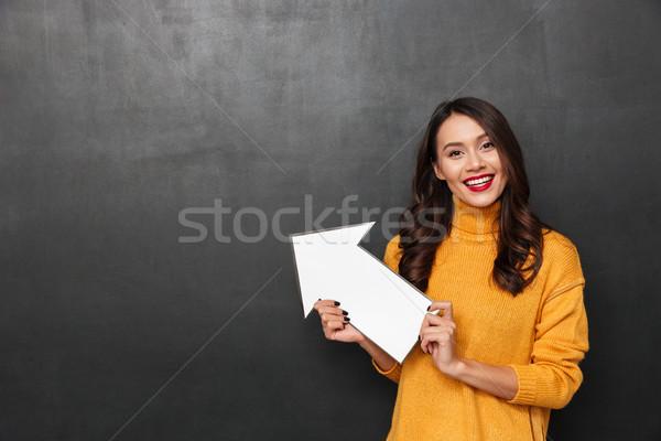 Sorridente morena mulher suéter indicação papel Foto stock © deandrobot