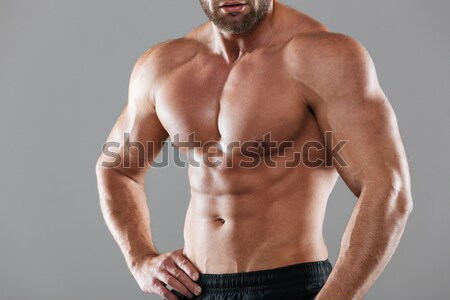 Cropped image of a muscular strong shirtless male bodybuilder Stock photo © deandrobot