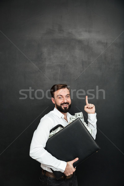 Stock photo: Picture of optimistic man rejoicing his prize hugging black brie
