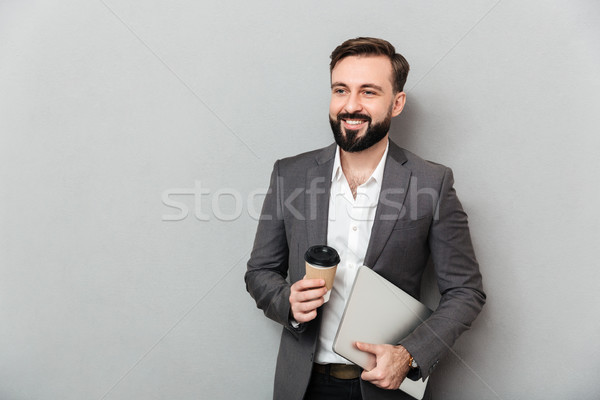 Portrait of cheerful male office worker posing on camera holding Stock photo © deandrobot