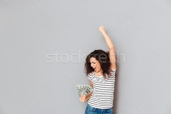 Emotional woman in striped t-shirt acting like winner holding fa Stock photo © deandrobot