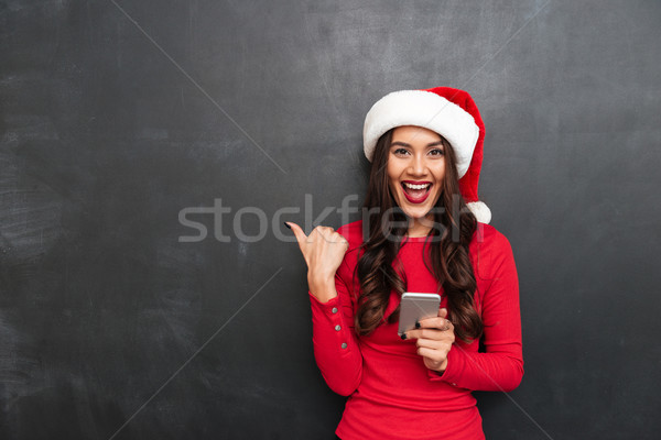 Cheerful brunette woman in red blouse and christmas hat Stock photo © deandrobot