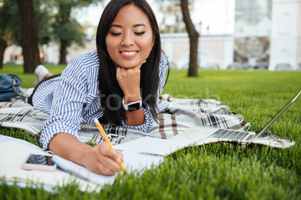 Pretty asian female student taking notes, lying on checkered pla Stock photo © deandrobot