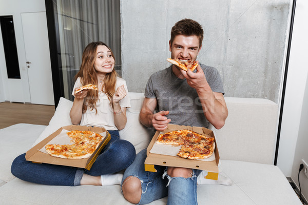 Delighted young couple eating pizza Stock photo © deandrobot
