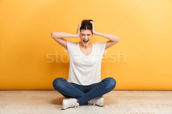 Portré bosszús fiatal nő ül lábak keresztbe padló Stock fotó © deandrobot
