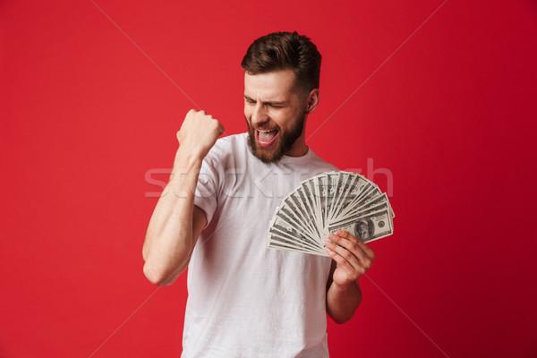 Izgatott sikít fiatalember tart pénz gyártmány Stock fotó © deandrobot