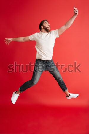 Stockfoto: Portret · gelukkig · jonge · man · zonnebril · springen