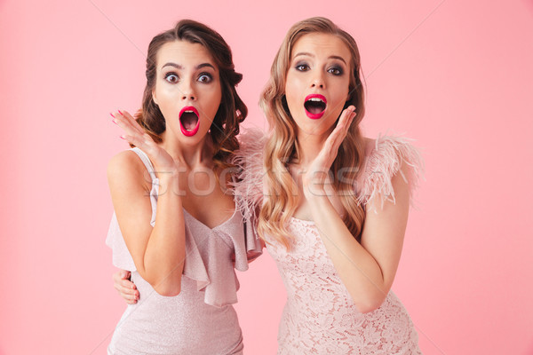 Two shocked women in dresses hugging to each other Stock photo © deandrobot