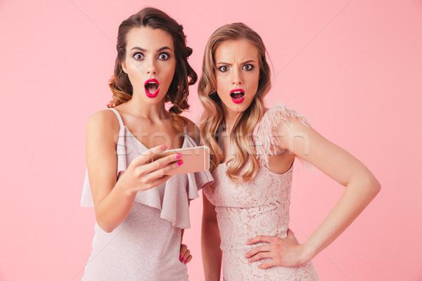 Stock photo: Two Shocked elegant women in dresses holding smartphone