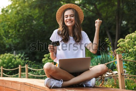 Delighted young girl sitting with laptop Stock photo © deandrobot