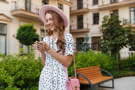 Pretty young woman holding hand of her boyfriend while walking o Stock photo © deandrobot
