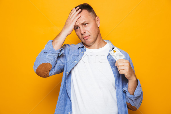 Portrait of an upset middle aged man holding credit card Stock photo © deandrobot