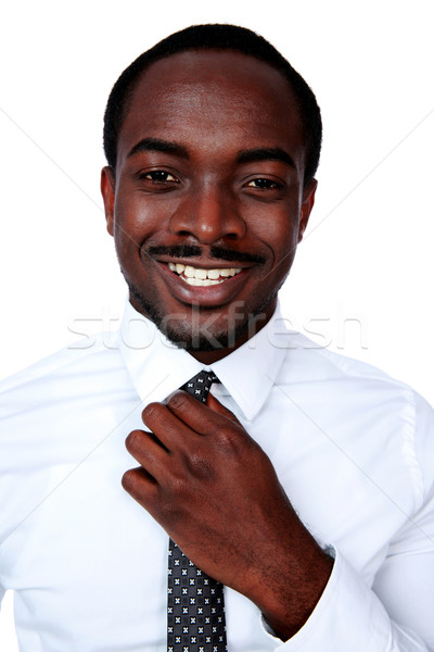 Happy african man adjusting his necktie over white background Stock photo © deandrobot