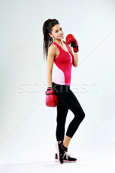 Young smiling sports woman standing with boxing gloves on gray background Stock photo © deandrobot