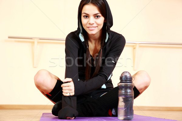 Genç gülen uygun kadın oturma yoga mat Stok fotoğraf © deandrobot
