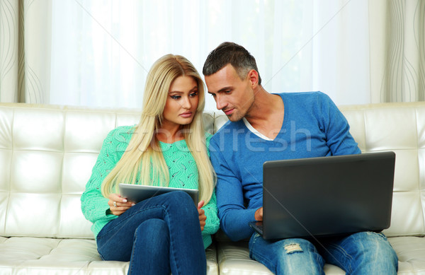 Young couple sitting on the sofa and using tablet computer with laptop at home Stock photo © deandrobot
