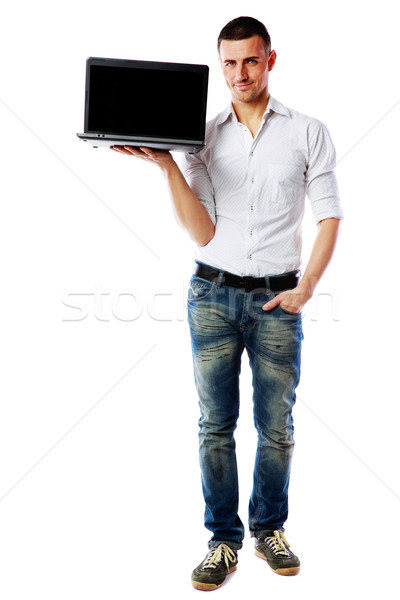 Full-length portrait of a happy man with laptop over white background Stock photo © deandrobot