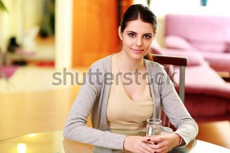 Fiatal boldog nő ül asztal tart Stock fotó © deandrobot