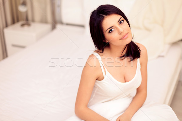 Young beautiful serene woman sitting on the bed at home Stock photo © deandrobot