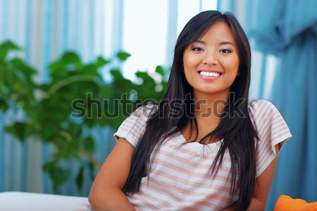 Happy young asian woman browsing internet with her tablet Stock photo © deandrobot