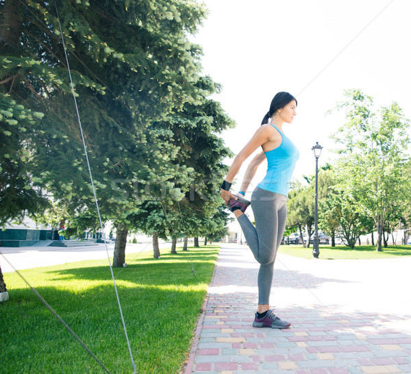 Sports woman stretching legs outdoors Stock photo © deandrobot
