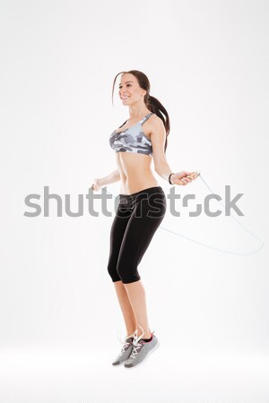 Fitness woman stretching with skipping rope Stock photo © deandrobot