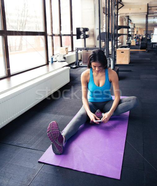 Young woman sitting on the yoga mat and using smartphone Stock photo © deandrobot