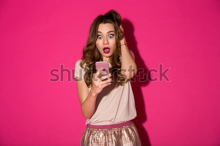 Surprised young woman talking on the phone Stock photo © deandrobot