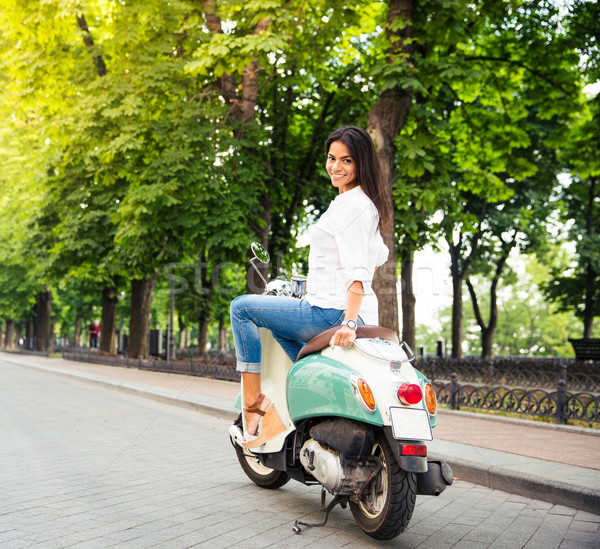 Happy young woman on a scooter Stock photo © deandrobot