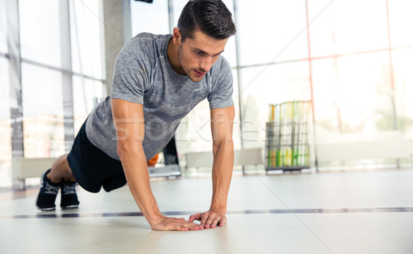 Man doing push-ups in gym Stock photo © deandrobot