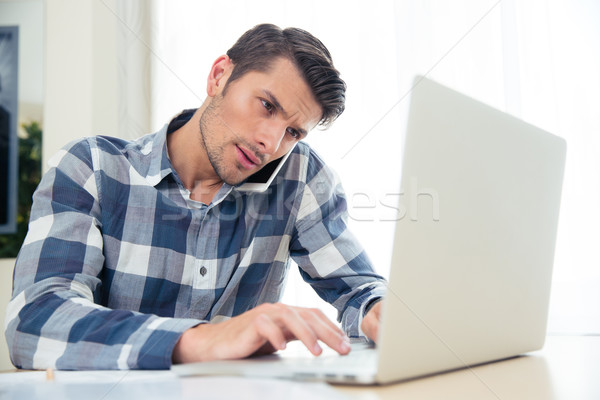 Man paying his bills with laptop while talking on phone Stock photo © deandrobot