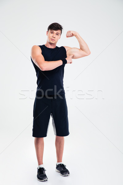 Fitnessz férfi mutat bicepsz teljes alakos portré Stock fotó © deandrobot