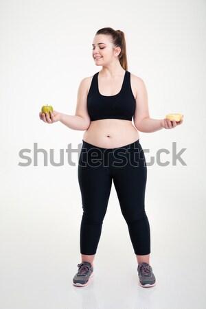 Fat woman choosing between donut and apple Stock photo © deandrobot