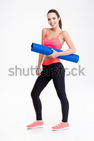 Attractive smiling young fitness woman holding yoga mat  Stock photo © deandrobot