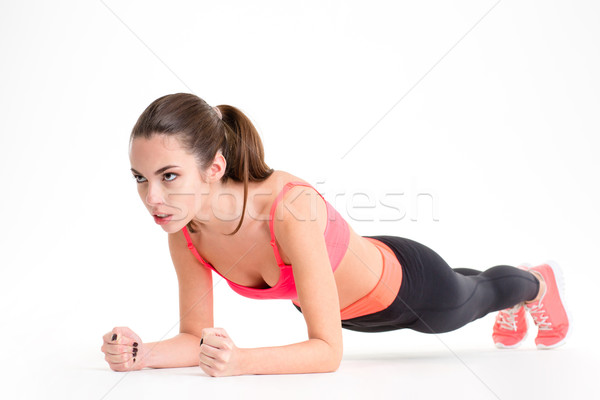 Concentrated beautiful fitness girl in sportwear exercising doing plank  Stock photo © deandrobot