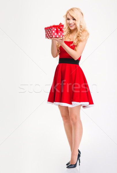 Joyful anticipated young woman in santa claus costume opening gift  Stock photo © deandrobot