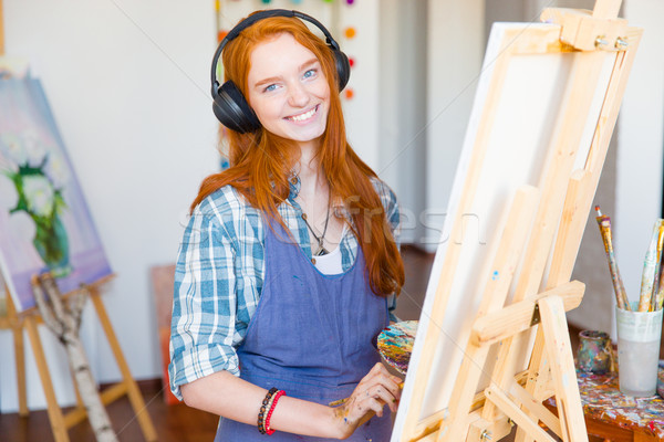 Smiling woman artist painting on canvas and listening to music Stock photo © deandrobot